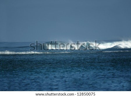 Active waves curl and roll toward shore.  Aqua and blue waters with blue sky.  Spray and foam. - stock photo