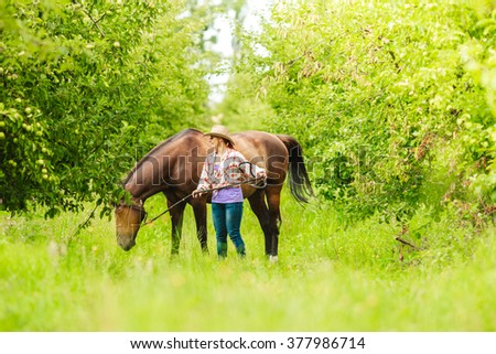 Active western cowgirl woman in hat walking with horse. American girl in countryside ranch. - stock photo
