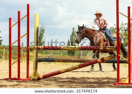 Active western cowgirl woman training riding horse jumping over fence. Equestrian sport competition and activity. - stock photo