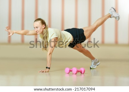 Active woman doing yoga exercises in gym