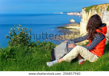 Active woman hiking and looking at beautiful ocean view, vacation in Etretat, France