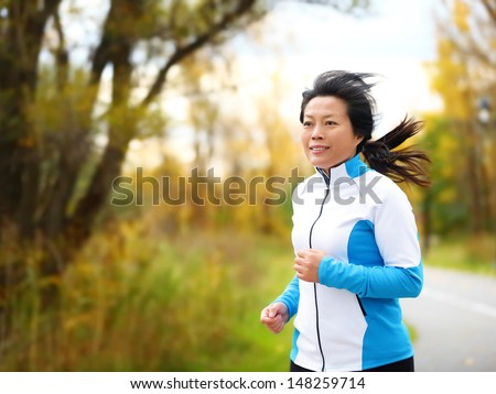 Active woman in her 50s running and jogging. Middle aged Asian mature female jogger outdoor living healthy lifestyle in beautiful autumn city park in colorful fall foliage. Asian Chinese adult fifties - stock photo
