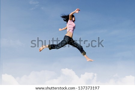 Active woman is jumping over the clouds