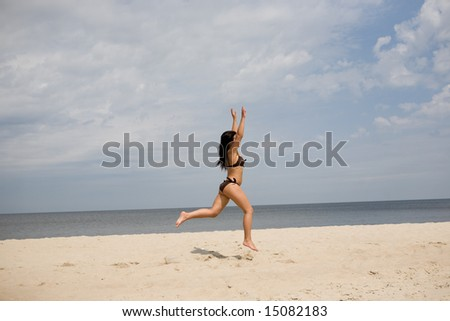 active woman jumping on the beach