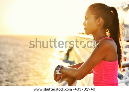 Active woman relaxing after run on cruise ship looking at the sea during summer holidays. Asian runner girl wearing smartwatch heart rate activity monitor living a healthy lifestyle.