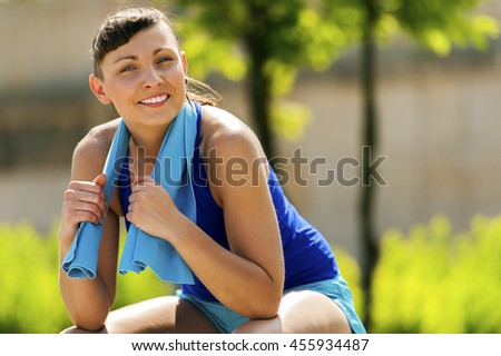 Active woman resting after jogging with towel. Smiling.
