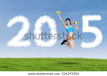 Active woman wearing sporsts wear, jumping on meadow with two dumbbells and forming number 2015 - stock photo