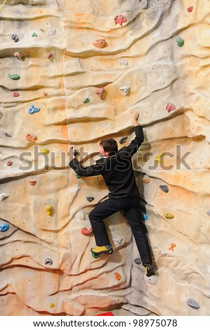 active young business man on rock wall in sport center - stock photo