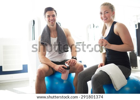 Active Young Couple Relaxing on Exercise Ball After Workout In the Gym and Smiling at the Camera - stock photo
