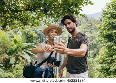 Active young couple taking self portrait. Man and woman on vacation in forest taking selfie with their mobile phone. - stock photo