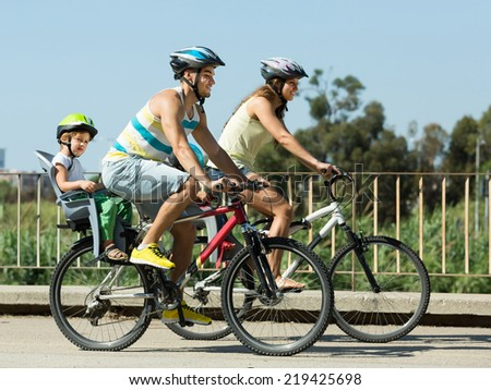 Active young family with two little daughters traveling by bicycles. Focus on man  - stock photo
