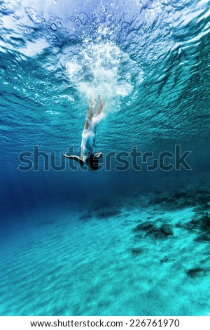 Active young female dancing underwater, enjoying summer vacation in blue transparent water, dive to the bottom of sea, enjoyment and freedom concept - stock photo