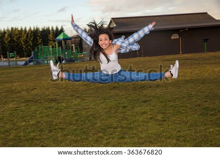 Active young girl jumping and doing the splits midair - stock photo