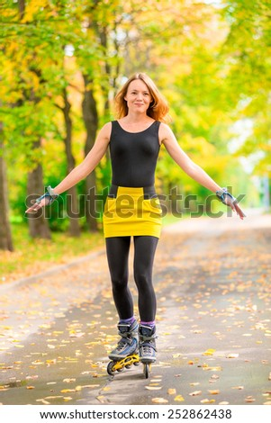 active young girl roller-skating in the autumn park  - stock photo