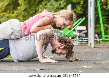 Active young man and woman exercising doing push ups. Muscular strong guy and girl in training suit working out at outdoor gym. Sport fitness and healthy lifestyle concept. - stock photo
