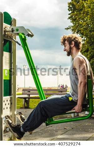 Active young man exercising on leg press machine. Muscular strong guy in training suit working out at outdoor gym. Sport fitness and healthy lifestyle concept.