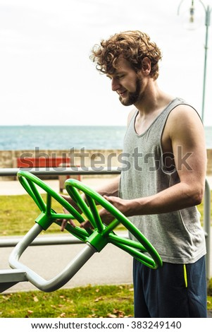 Active young man exercising with tai chi wheel. Muscular sporty guy in training suit working out at outdoor gym. Sport fitness and healthy lifestyle concept.