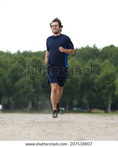 Active young man smiling and jogging outdoors