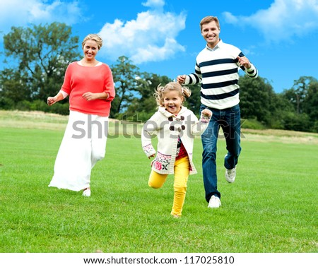 Active young parents running to catch their daughter. Fun loving family - stock photo