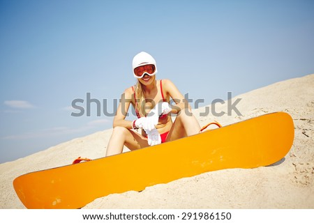 Active young sandboarder in red bikini sitting on sand