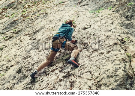 Active young woman climbing on rock outdoor in summer - stock photo