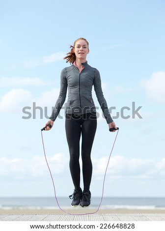 Active young woman jumping with skipping rope outdoors - stock photo
