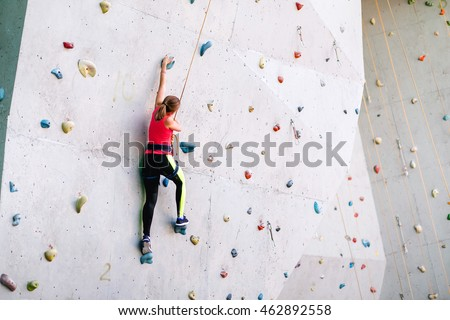 active young woman on rock wall in sport center