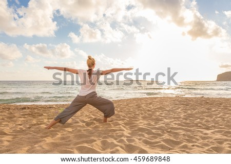 Active young woman practicing yoga on beach at sunset.
