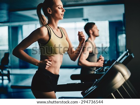Active young woman running on treadmill with guy on background - stock photo