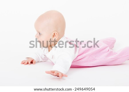 actively crawling wearing a romper baby. studio photo
