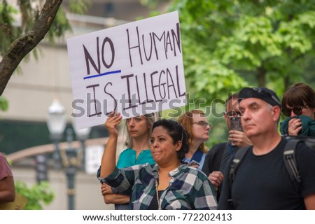 Activists signs express support for immigrant community at a rally to protest president Donald Trump's decision to end DACA Downtown Portland, OR, on September 5th, 2017.