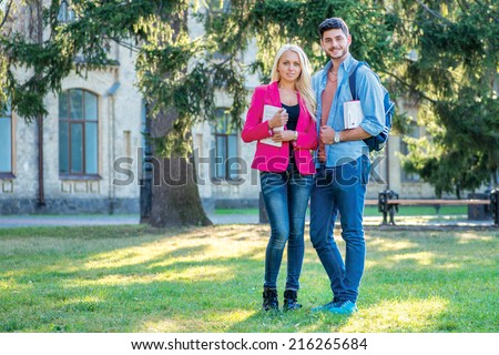 Activities outside the university. Couple of students standing together holding books looking at the camera while standing on the grass against the building of the university - stock photo