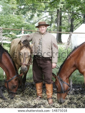 Actor in costume with his horses for re-enactment of civil war