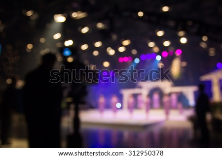 Actress or singer in studio of television station with camera and cameraman - stock photo