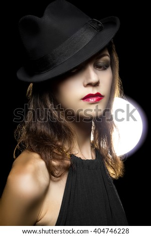 Actress with classic smoky dark make up in Hollywood film noir style.  Her cosmetic make up style is dark and a retro look.