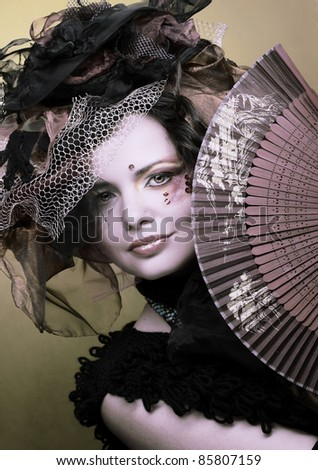 Actress. Young woman in creative image with fan.