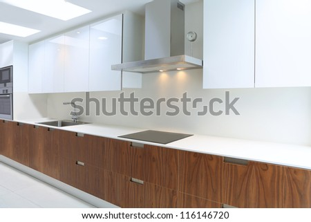 Actual modern kitchen in white and walnut wood interior house - stock photo