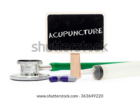ACUPUNCTURE concept with text on chalkboard with stethoscope, syringe and pills - stock photo