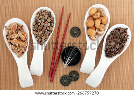 Acupuncture needles and chinese herbal medicine selection with chopsticks and I ching coins over bamboo background. - stock photo