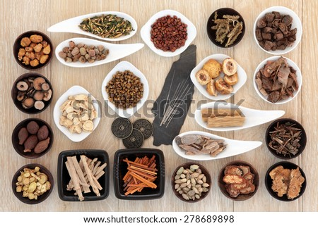 Acupuncture needles and chinese herbal medicine selection with I Ching coins. - stock photo