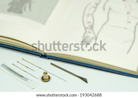 Acupuncture needles and textbook - stock photo