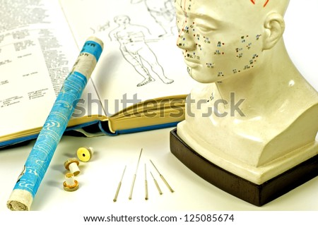 Acupuncture needles, head model, textbook and moxa roll - stock photo