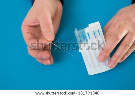 Acupuncture needles in doctor hands holding blister on blue - stock photo