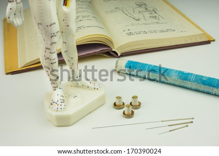 Acupuncture needles,  model, textbook and moxa roll - stock photo