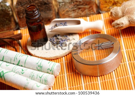 Acupuncture needles, moxa sticks, lavender petals with macerated oil, giner and herbs in jars. TCM Traditional Chinese Medicine concept photo