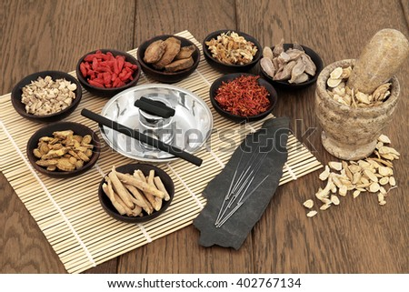 Acupuncture needles, moxa sticks, traditional chinese herbs for herbal medicine and mortar with pestle over bamboo and old oak background. - stock photo