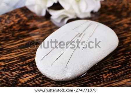 Acupuncture needles on wooden plate with spa stone, closeup - stock photo