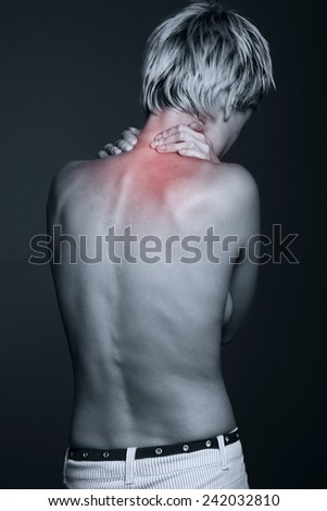 Acute pain in a neck at the young women. young girl keeps for a sick neck on a black background  - stock photo