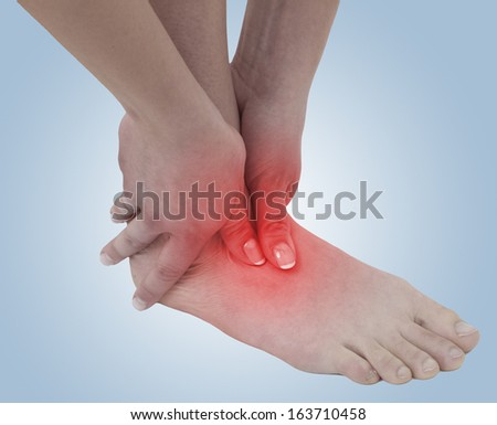 Acute pain in a woman ankle. Concept photo with blue skin with read spot indicating pain.
