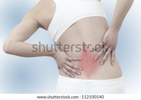Acute pain in a woman back. Female from behind holding hand to spot of back pain. Concept photo with Color Enhanced skin with read spot indicating location of the pain. - stock photo